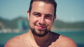 Le jeune Caucasien de portrait haut étroit de l'homme bel de brune une barbe regardant dans la caméra réfléchie, sourit songeur,  banque de vidéos