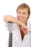 Le jeune chanteur se penche des coudes sur la guitare et rit Image stock