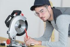 Le jeune charpentier employant la circulaire a vu pour le bois à l'intérieur de l'entrepôt photographie stock