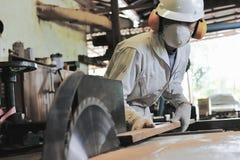 Le jeune charpentier professionnel avec le dispositif de protection coupant un morceau de bois sur la table a vu la machine dans  Photo stock