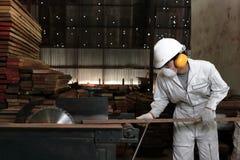 Le jeune charpentier professionnel avec le dispositif de protection coupant un morceau de bois sur la table a vu la machine dans  Image libre de droits