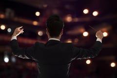 Le jeune chef d'orchestre avec le bâton a augmenté à une interprétation, vue arrière Image stock