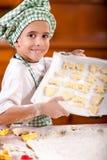 Le jeune chef de garçon montre les biscuits disposés pour la cuisson photos libres de droits