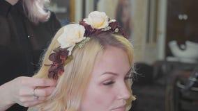 Le jeune coiffeur féminin met une guirlande à la femme assez blonde au salon beaty de luxe banque de vidéos
