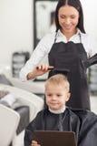 Le jeune coiffeur gai utilise le dessiccateur dedans images libres de droits