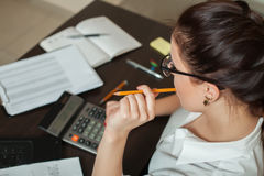 Le jeune comptable féminin considère sur la calculatrice images stock