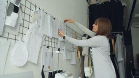 Le jeune concepteur de vêtements créatif regarde des croquis les accrochant alors sur le mur au-dessus de la table de studio près banque de vidéos