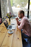 Le jeune concepteur prometteur s'asseyant dans le studio pour un ordinateur portable et développe la collection de concepteur Images stock