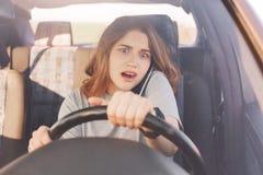 Le jeune conducteur femelle mignon étonné a la conversation téléphonique par l'intermédiaire du téléphone portable, conduit la vo Images stock