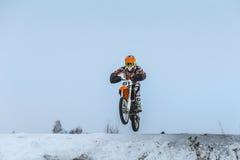 Le jeune conducteur sur la moto saute par-dessus la montagne Image stock