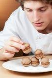 Le jeune confiseur de chef met des gâteaux mousseline sur la plaque images libres de droits