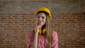 Le jeune constructeur butiful de fille a l'idée, processus de pensée, fond de brique clips vidéos