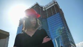 Le jeune constructeur fort de fille avec le hemlet se tient avec des bras croisés pendant la journée en été, concept de construct clips vidéos