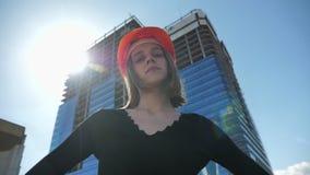 Le jeune constructeur fort de fille avec le hemlet se tient avec des bras croisés pendant la journée en été, observant à l'appare clips vidéos