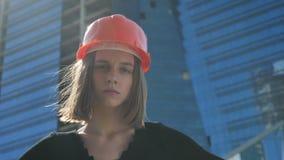 Le jeune constructeur fort de fille avec le hemlet se tient avec des mains sur des hanches pendant la journée en été, concept de  clips vidéos