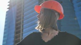 Le jeune constructeur fort de fille avec le hemlet se tient avec des mains sur des hanches pendant la journée en été, tête de rot banque de vidéos