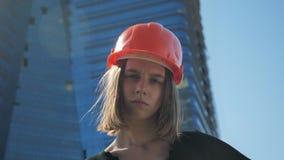 Le jeune constructeur fort de fille avec la hameau montre le poing dans la journée en été, concept de construction, concept urbai banque de vidéos