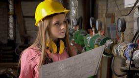 Le jeune constructeur sérieux de fille observe le plan du bâtiment, pensant banque de vidéos