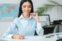 Le jeune consultant en matière féminin d'agent de voyage dans l'écriture d'agence de visite et communiquent à l'aide du casque photographie stock libre de droits