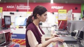 Le jeune costume femelle ouvre l'ordinateur portable de la rangée d'étalage pour l'examiner Choix de la nouvelle électronique dom banque de vidéos