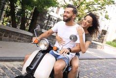 Le jeune couple élégant repose un scooter dans la rue Photo stock
