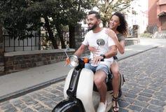 Le jeune couple élégant repose un scooter dans la rue Photographie stock libre de droits