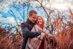 Le jeune couple étreint dans la forêt d'automne parmi la haute herbe Photo stock