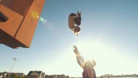 Le jeune couple acrobatique exécutant la secousse, jeune homme jette une femme dans le ciel équilibrant sur ses bras au coucher d clips vidéos
