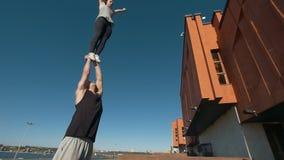 Le jeune couple acrobatique exécutant la secousse, jeune homme jette une femme dans le ciel équilibrant sur ses bras au coucher d banque de vidéos