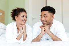 Le jeune couple affectueux africain de sourire se trouve sur le lit à l'intérieur Images stock