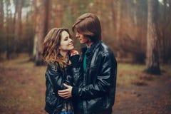 Le jeune couple affectueux heureux dans des vestes en cuir étreint extérieur sur la promenade confortable dans la forêt Photos stock