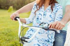 Le jeune couple affectueux monte la bicyclette en parc Photos stock