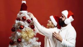 Le jeune couple affectueux orne un arbre de Noël sur un fond rouge L'homme barbu étreint la femme qui décore l'arbre de Noël dess banque de vidéos