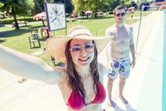 Le jeune couple affectueux près de la piscine prend un selfie Image stock