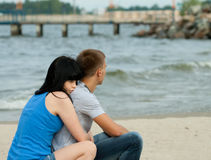 Le jeune couple affectueux se repose près de la mer photographie stock