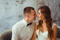 Le jeune couple attrayant repose le sourire sur le divan démodé Images libres de droits