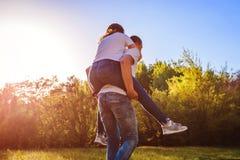 Le jeune couple dans l'amour ayant l'homme de forêt d'amusement au printemps monte son amie dessus de retour au coucher du soleil Photo stock