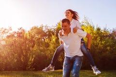 Le jeune couple dans l'amour ayant l'homme de forêt d'amusement au printemps monte son amie dessus de retour au coucher du soleil Image stock