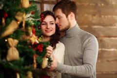 Le jeune couple dans l'amour décore l'arbre de Noël à la maison Image libre de droits