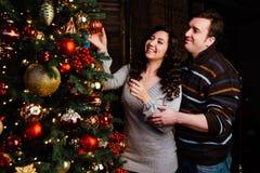 Le jeune couple dans l'amour décore un arbre de Noël à la maison Images libres de droits