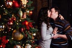 Le jeune couple dans l'amour décore un arbre de Noël à la maison Photographie stock libre de droits