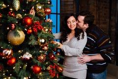 Le jeune couple dans l'amour décore un arbre de Noël à la maison Image stock