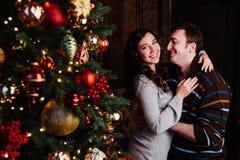 Le jeune couple dans l'amour décore un arbre de Noël à la maison Photo libre de droits