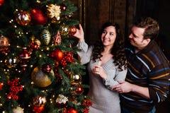 Le jeune couple dans l'amour décore un arbre de Noël à la maison Image libre de droits