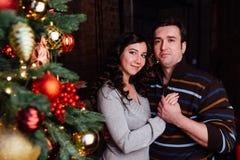 Le jeune couple dans l'amour décore un arbre de Noël à la maison Photo stock
