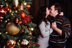 Le jeune couple dans l'amour décore un arbre de Noël à la maison Photos stock