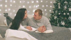Le jeune couple dans l'amour en décor de nouvelle année avec les cadeaux et l'arbre de Noël, là est bruit dans la vidéo clips vidéos