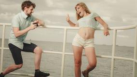 Le jeune couple dans l'amour prend des photos sur la jetée de mer Photographie stock