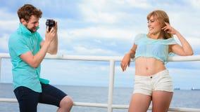 Le jeune couple dans l'amour prend des photos sur la jetée de mer Image libre de droits