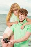 Le jeune couple dans l'amour prend des photos sur la jetée de mer Images libres de droits